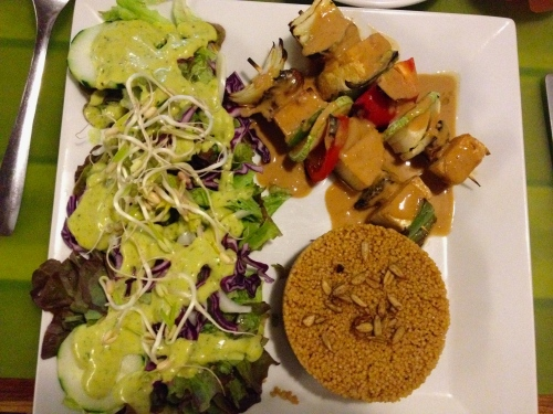 Vegan dinner of couscous, salad with cashew dressing and tofu kebabs with peanut satay sauce